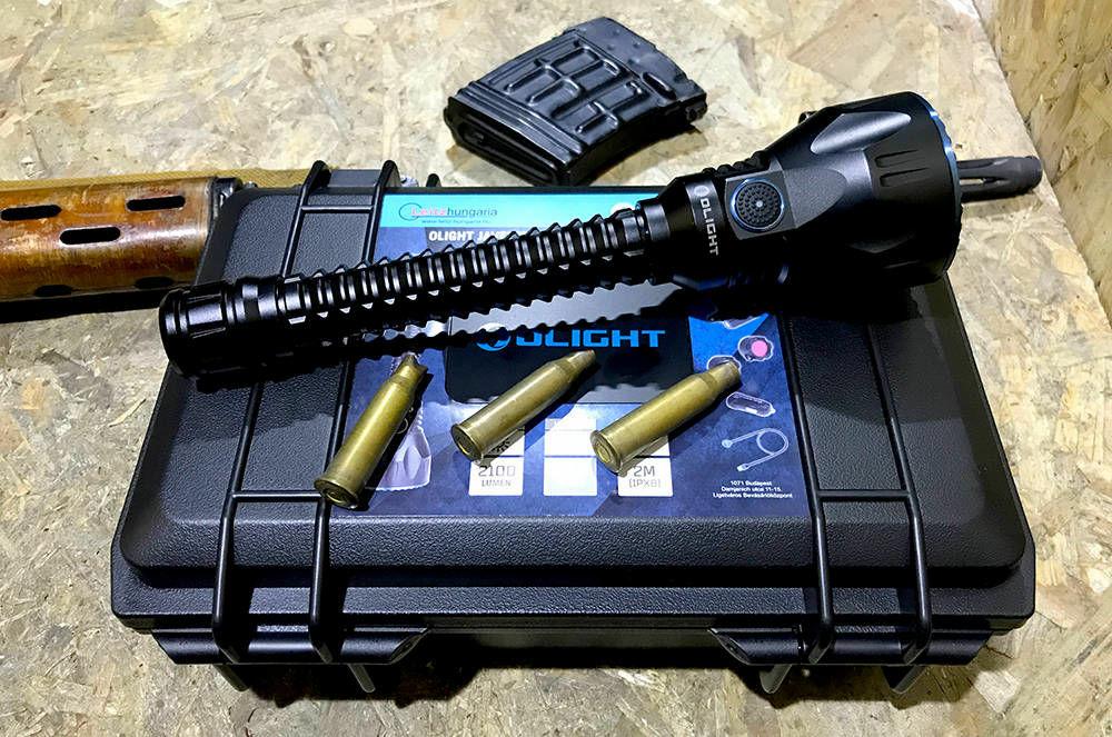 A képen fegyver, lőfegyver, ülő, asztal láthatóAutomatikusan generált leírás